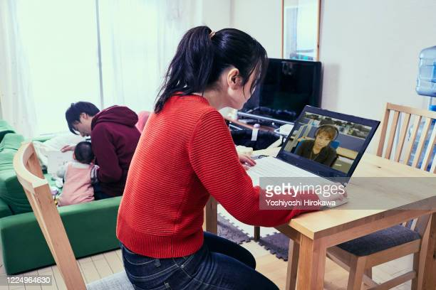 """father takes care of daughter and mother is busy working from home - leanincollection """"working mom"""" stock pictures, royalty-free photos & images"""