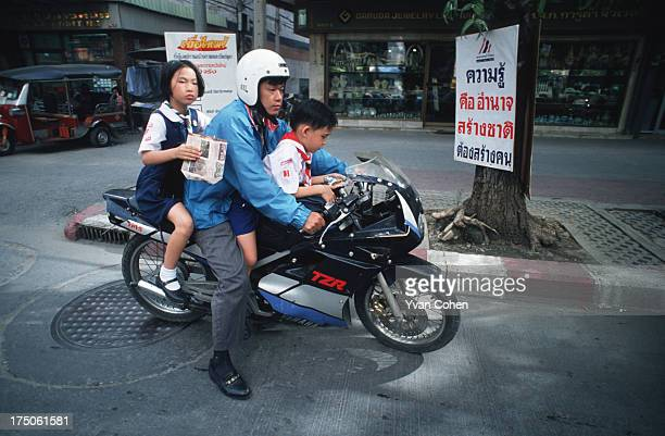 A father takes his children to school on the family motorcycle Even though helmets are compulsory for motorcyclists in Bangkok parents often neglect...