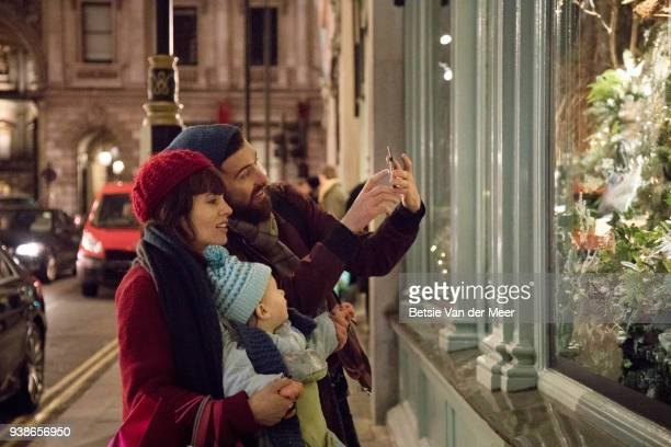 Father takes photo of  christmas display in store window, mother and child look on.