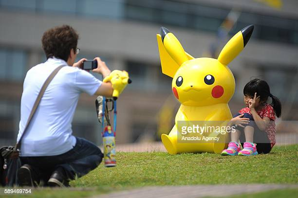 A father takes photo of his daugther enjoying the summer holidays as they take part to the Pikachu dance event the most well known pocket monster...