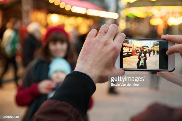 Father takes photo of mother and child on mobile phone outdoors.
