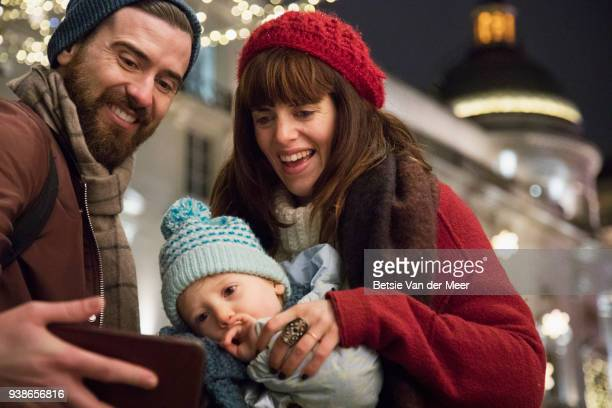 Father takes selfie of mother and child in shopping street with christmas lights.