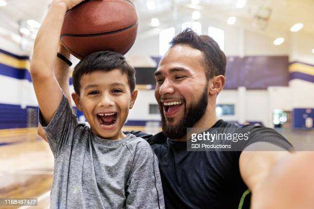 father takes selfie while son holds a basketball on head - estilo de vida ativo imagens e fotografias de stock