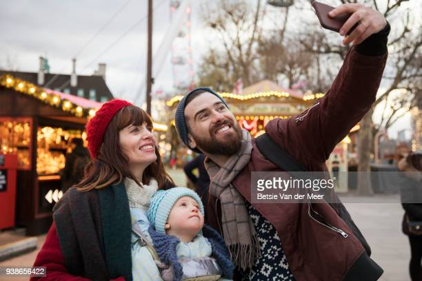 Father takes selfie with wife and son at christmas market.