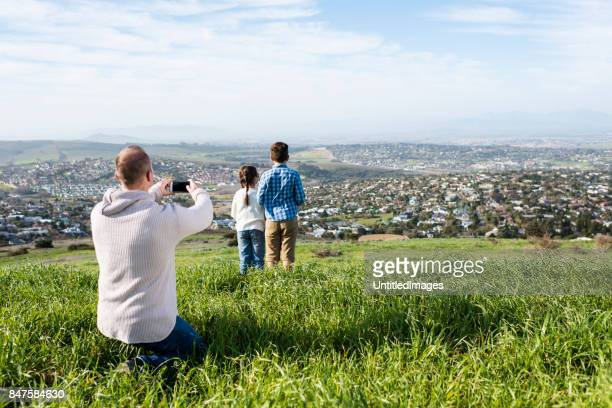 Father taking a photo of brother and daughter