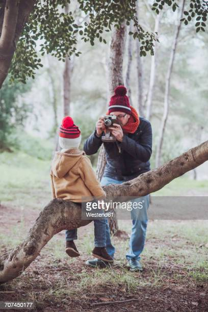 Father taking a picture of his son sitting on tree trunk in forest