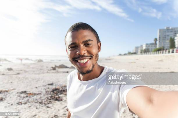 father taking a selfie of himself on the beach. - self portrait stock pictures, royalty-free photos & images