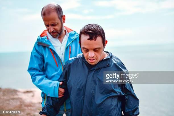 padre dando un paseo con su hijo discapacitado - discapacidad intelectual fotografías e imágenes de stock