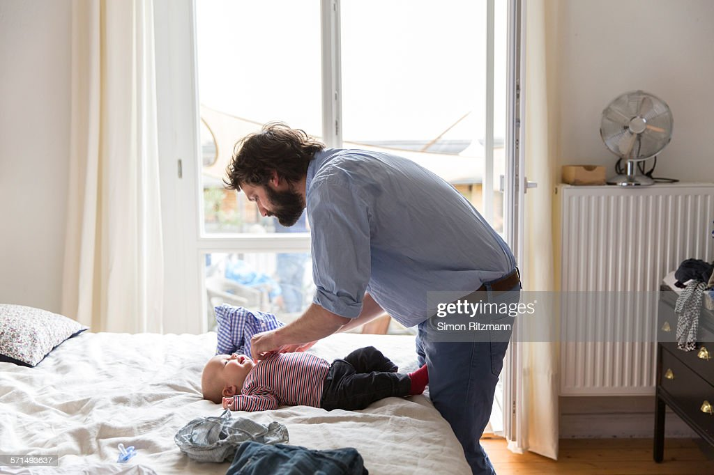Father taking care of baby son at home : Stock Photo