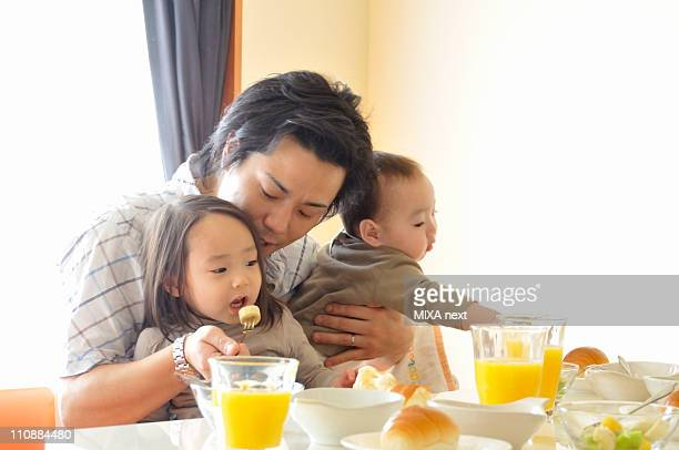 Father Taking Care of Children at Breakfast Table