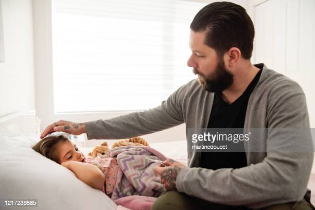 """father taking care of sick little girl lying in bed with thermometer. - """"martine doucet"""" or martinedoucet imagens e fotografias de stock"""