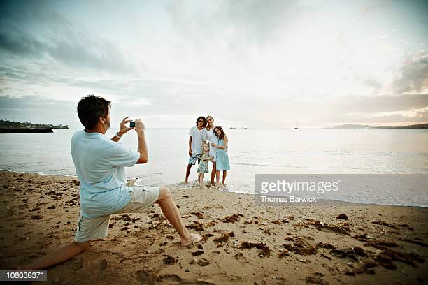 Father taking digital photo of family at sunset