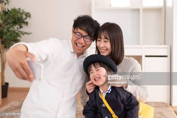 スマートフォンで家族の肖像画を撮る父 - 撮影テーマ ストックフォトと画像