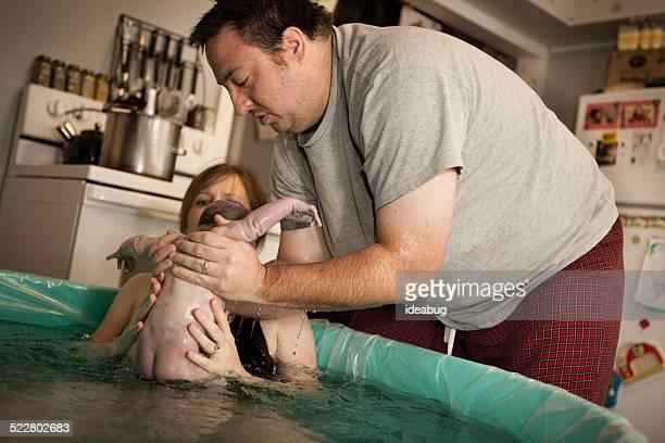 Padre tomar recién nacido en bañera de partos agua nacimiento en casa