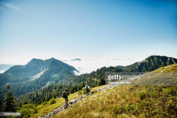 father taking photo of daughter hiking on trail across mountain - mid distance stock pictures, royalty-free photos & images