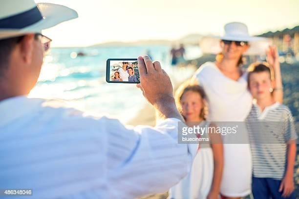 Padre tomar fotografías de su familia en la playa