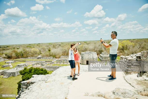 Father taking photo of kids taking selfie with smartphone while exploring Mayan ruins during vacation