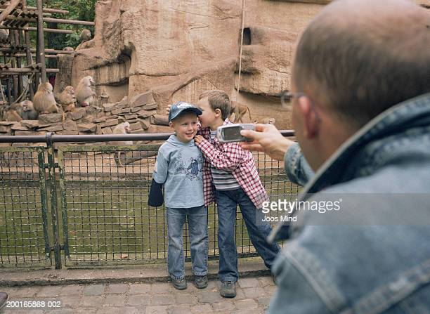Father taking photo of sons (3-6) by baboon enclosure in zoo