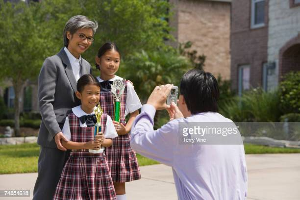 Father taking photograph of family with trophies