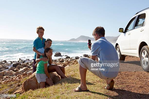 Father taking picture of family by sea