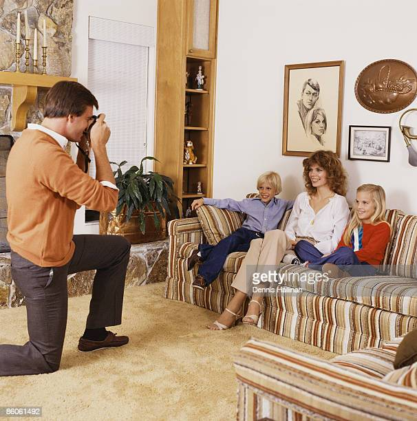 Father taking picture of family in living room