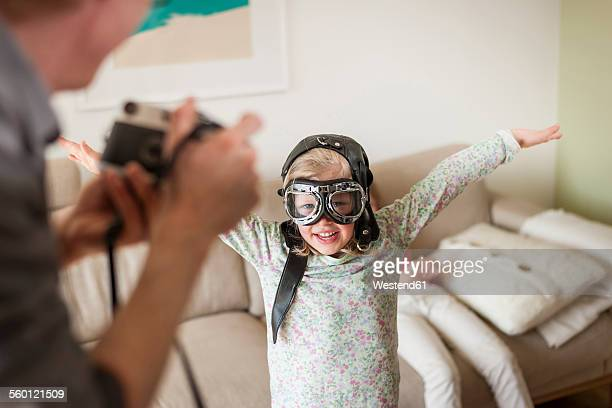 Father taking picture of girl pretending to fly
