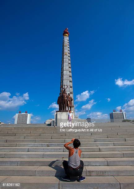 Father taking picture of her daughter in front of juche tower pyongyang North Korea on September 9 2012 in Pyongyang North Korea