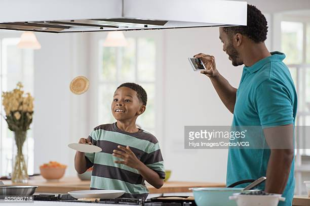 Father taking picture of son (10-12) tossing pancake