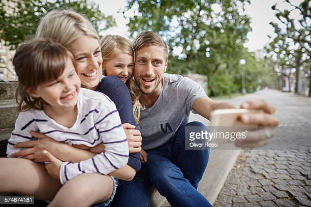 Father taking selfie of happy family on bench