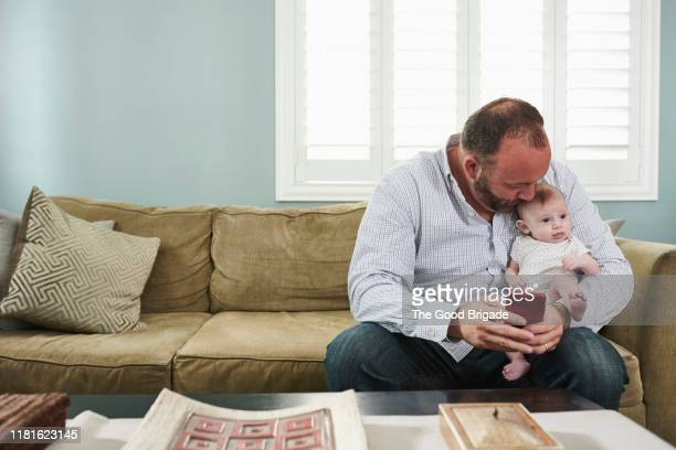 father taking selfie with baby on sofa in living room - lgbtq  and female domestic life fotografías e imágenes de stock