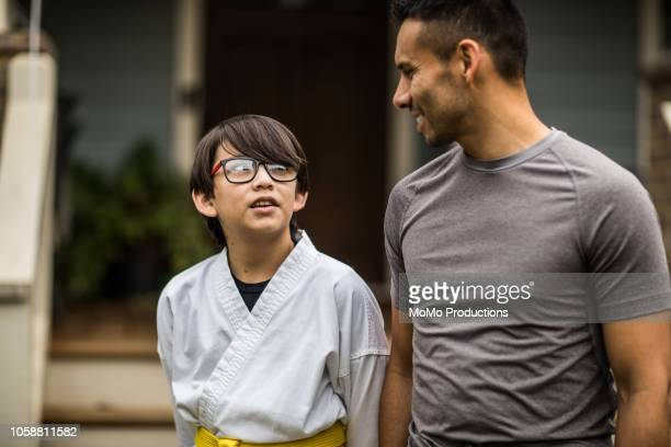 father taking young boy to karate practice - gray shirt stock pictures, royalty-free photos & images