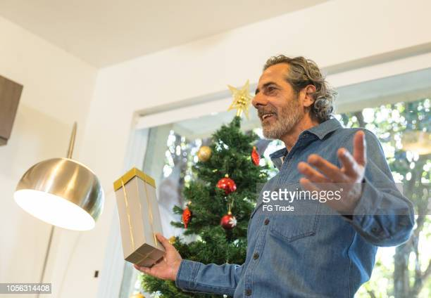 father talking about your secret friend in a game with christmas gift at amigo secreto in brazil - men wearing stockings stock photos and pictures