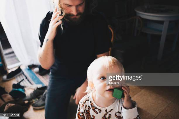 Father talking on mobile phone while girl playing with toy at home