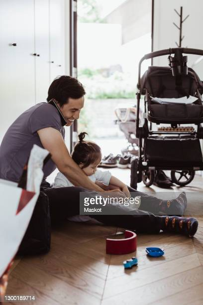 father talking on smart phone while tying baby son's shoelace at home - carriage stock pictures, royalty-free photos & images