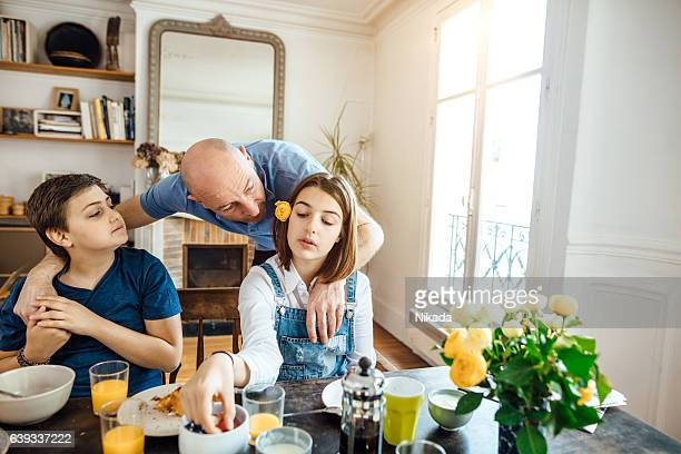 Father talking to children having breakfast at home