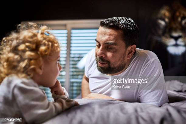 Father talking to daughter in bed