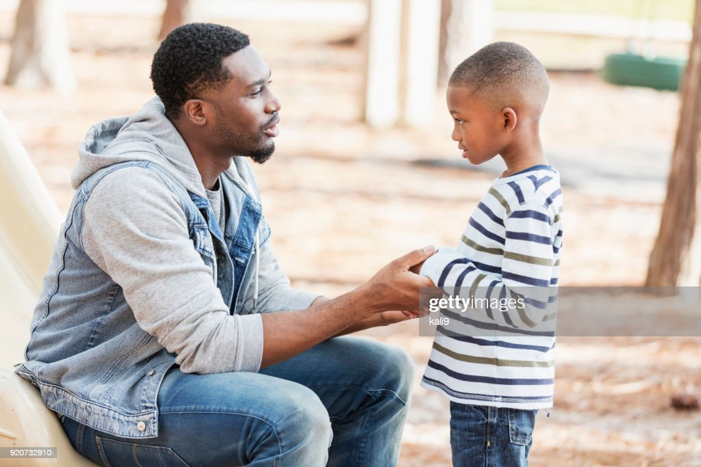 Father talking to little boy on playground : Stock Photo