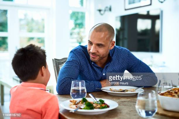 father talking to son at dinner table - parent stock pictures, royalty-free photos & images