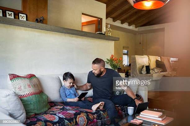 Father talking to son using tablet computer in living room