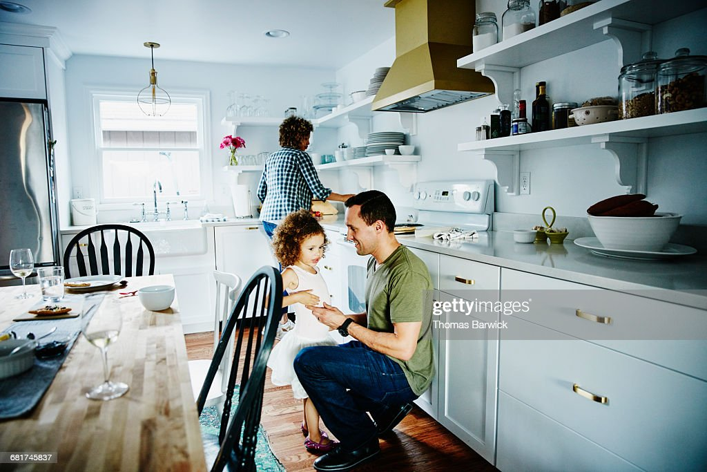 Father talking to young daughter in kitchen : Stock Photo