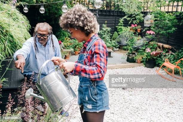 father talking with daughter while gardening at backyard - daughter stock pictures, royalty-free photos & images