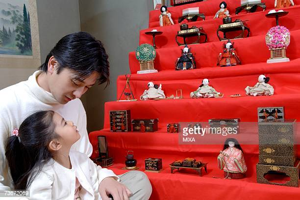 Father talking with his daughter in front of dolls