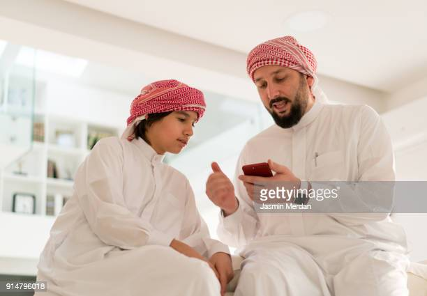 Father talking with his son using smart phone