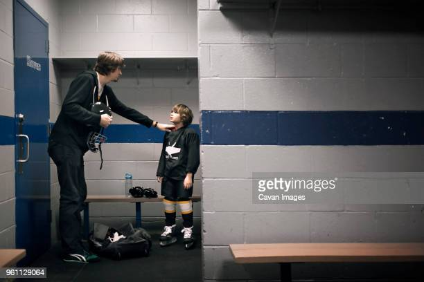 father talking with son in locker room - young boys changing in locker room stock pictures, royalty-free photos & images