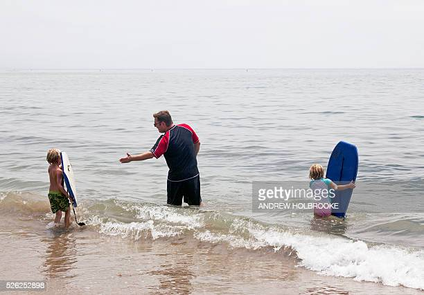 A father talks to his son His children with boogy boards in the water at Miramar Beach on the Pacific Ocean Montecito is a wealthy beach community...