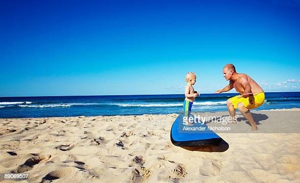 Father teach son to surf on land
