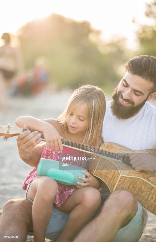 Father teaches his daughter how to play the guitar. : Stock Photo