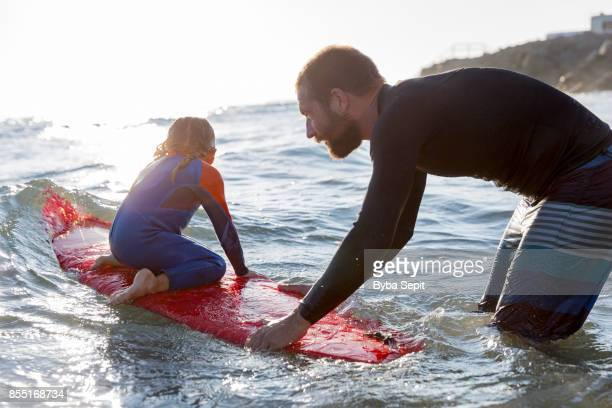 Father teaches his little daughter surfing.