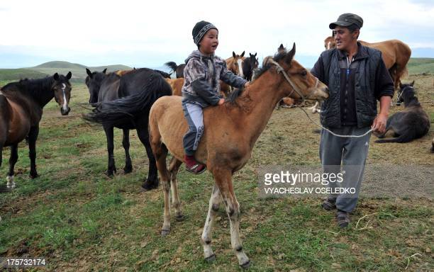 Father teaches his son to ride a horse at a pasture of the Suu-Samyr plateau 500 meters above the sea level, along the ancient Great Silk Road from...