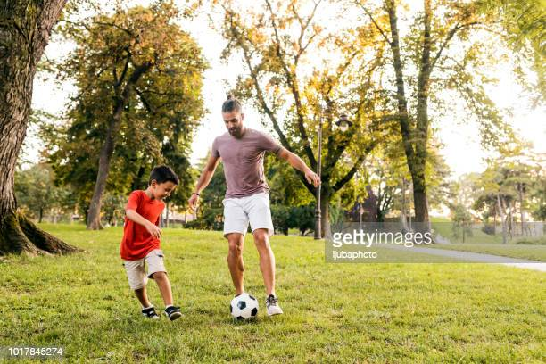 father teaches son how to play football - passing sport imagens e fotografias de stock